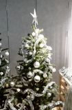 White and silver decorative Christmas tree with tinsel garland,. Glitter balls, and silver star for interior seasonal greeting royalty free stock photography