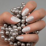 White silver glittered nails manicure. The female hand with white and silver glittered nails is holding pearls on gray background. Manicure and nail art concept Stock Photography