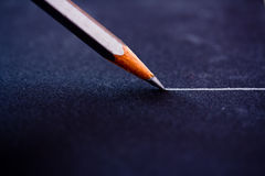 White/silver pencil writing lines on black. Macro shot of a silver/white pencil writing a straight line on black paper royalty free stock photo