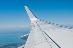 White silver plane wing flying in blue sky Royalty Free Stock Photos