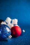 White, silver and red xmas ornaments on dark blue glitter background with space for text. Stock Photography