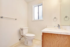 White simple bathroom interior with small window. White simple bathroom interior with small window, toilet and vanity cabinet. Northwest, USA Stock Images