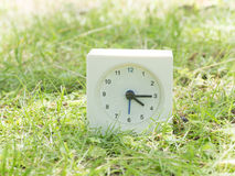 White simple clock on lawn yard, 4:15 four fifteen Stock Photos