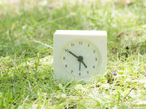 White simple clock on lawn yard, 4:50 four fifty Stock Photos