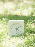 White simple clock on lawn yard, 4:10 four ten. White rectangle simple clock on lawn yard, 4:10 four ten Royalty Free Stock Photography