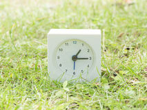 White simple clock on lawn yard, 1:15 one fifteen Royalty Free Stock Photos