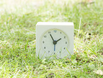 White simple clock on lawn yard, 1:55 one fifty five Royalty Free Stock Image
