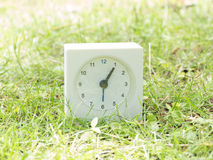White simple clock on lawn yard, 1:05 one five Royalty Free Stock Images