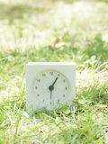 White simple clock on lawn yard, 1:05 one five Stock Image