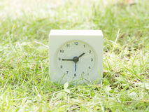 White simple clock on lawn yard, 1:45 one forty five Stock Photography