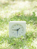 White simple clock on lawn yard, 1:45 one forty five Royalty Free Stock Photos