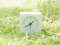 White simple clock on lawn yard, 1:40 one forty Royalty Free Stock Image