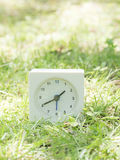 White simple clock on lawn yard, 1:40 one forty Stock Image