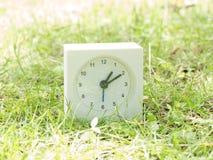 White simple clock on lawn yard, 1:10 one ten Stock Photo