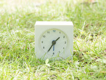 White simple clock on lawn yard, 1:35 one thirty five Royalty Free Stock Images