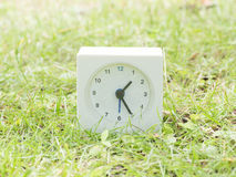 White simple clock on lawn yard, 1:25 one twenty five Stock Photography