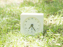 White simple clock on lawn yard, 7:25 seven twety five. White rectangle simple clock on lawn yard, 7:25 seven twety five Stock Image