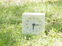 White simple clock on lawn yard, 6:15 six fifteen Royalty Free Stock Photos