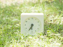 White simple clock on lawn yard, 6:35 six thirty five Stock Photo