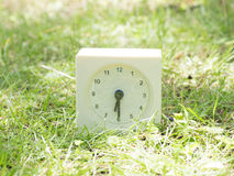 White simple clock on lawn yard, 6:30 six thirty half Royalty Free Stock Images