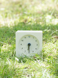 White simple clock on lawn yard, 6:30 six thirty half Stock Image