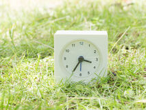 White simple clock on lawn yard, 3:35 three thirty five Stock Photo