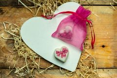 I love you - white, simple heart cut from wood on a romantic, simple rustic background next to two white, hearts shaped chocolates. White, simple heart cut from stock image