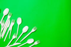 White single-use plastic knives, spoons, forks on a green background. Say no to single use plastic. Environmental, pollution royalty free stock photo