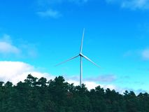 A white single wind generating by the highway. A white single wind generating against blue sky by the highway in Plymouth Massachusetts United States stock photos
