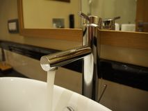 White sink chrome faucet in the included water in the hotel bathroom. White sink chrome faucet in the included water in hotel bathroom stock photography