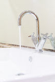 White sink washbasin and silver curve design faucet Royalty Free Stock Photo