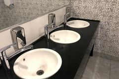 White sinks on the black tabletop in an interior of public toilet. Shiny chromed faucets and dispensers for liquid soap. Side view stock images