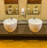White sinks and liquid soap in public toilet Stock Images