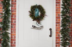 White skates hang with a spruce wreath. Christmas decoration of the front door of the house. White skates hang with a spruce wreath. Christmas decoration of the Stock Image