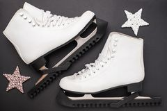 Skates and shiny stars on black background. royalty free stock photo
