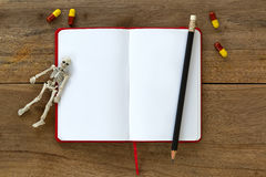 White skeleton dead body bones resting on blank white notebook w Stock Photography
