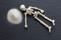 White skeleton dead body bones resting next to dangerous white f stock photo