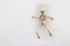 White skeleton trying to get out of a square grave. Made of snow during winter time Stock Photos