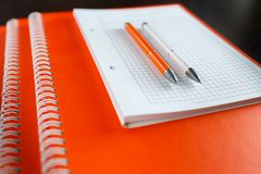 White sketchbook and orange notebooks lying on a dark brown wooden table with an orange and white pens. Business or financial planning Stock Photos