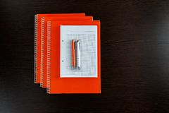 White sketchbook and orange notebooks lying on a dark brown wooden table with an orange and white pens. Ready for write plan, report or sketch drawing Royalty Free Stock Photo