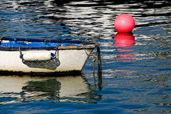 White Skiff With Pink Buoy. Small white skiff with a pink buoy/float reflected in harbour waters Royalty Free Stock Images