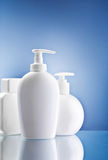 White skin care bottles on blue background Stock Images