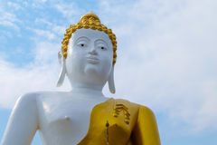 White skin with gold dress buddha sculpture. On clear sky royalty free stock images
