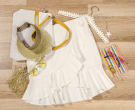 White skirt with ruffles and accessories arranged on the floor. Woman skirt with accessories, purse, sunglasses, visor and nail polish Royalty Free Stock Photo
