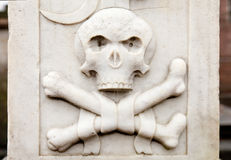 Bas-relief,  White Skull and crossbones on a gravestone Royalty Free Stock Images
