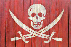 A white skull with swords symbolizing pirates on a red wood background Stock Image