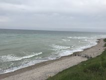 White sky over black sea. Sea water stormy grey clouds storm wet sand wind waves royalty free stock image