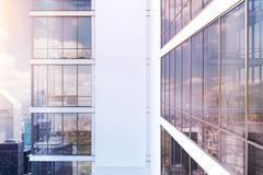 White skyscraper exterior, side, toned. Side view of an exterior of a white skyscraper with large windows and a gigantic poster between them. 3d rendering, mock Stock Photo
