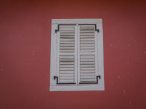 White Slat Wooden Window in Red Wall Stock Photo