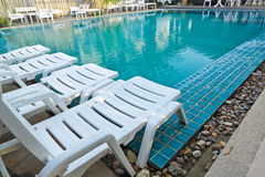 White sleeping chair and pool in light blue color Royalty Free Stock Image